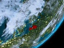 Opinión de la órbita de Letonia en la noche ilustración del vector