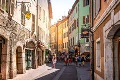 Opinión de la calle de la ciudad vieja de Annecy con los edificios históricos coloridos de los turistas y de la luz brillante her imagenes de archivo