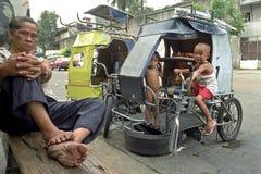 Opinión de la calle con el mecánico y los niños filipinos de la bici Fotos de archivo libres de regalías
