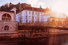 Opinión de la calle con puesta del sol en la igualación del puente viejo de la ciudad de Ljubljana fotografía de archivo