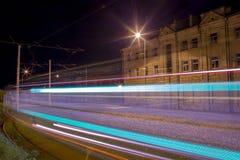 Opinión de la calle de la noche con los trazalíneas de la tranvía en la ciudad de Daugavpils Foto de archivo libre de regalías