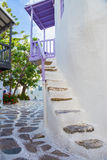 Opinión de la calle de Mykonos con las escaleras blancas, los árboles y el balcón púrpura, Grecia Fotos de archivo
