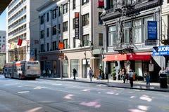 Opinión de la calle en San Francisco de peatones, de tiendas y de un autobús del MTA imagen de archivo