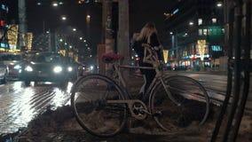 Opinión de la calle de la noche con los coches, la gente que camina y la bici izquierda almacen de metraje de vídeo