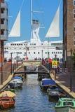 Opinión de la calle sobre un velero con las velas blancas Imagenes de archivo