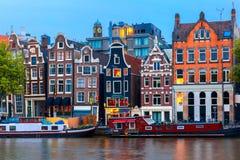 Opinión de la ciudad de la noche del canal de Amsterdam con las casas holandesas fotos de archivo libres de regalías