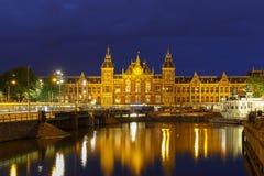 Opinión de la ciudad de la noche del canal de Amsterdam y de la estación de Centraal Fotografía de archivo libre de regalías