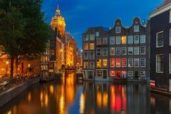 Opinión de la ciudad de la noche del canal, de la iglesia y del bri de Amsterdam foto de archivo