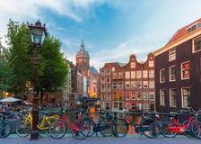 Opinión de la ciudad de la noche del canal, de la iglesia y del bri de Amsterdam Fotos de archivo libres de regalías
