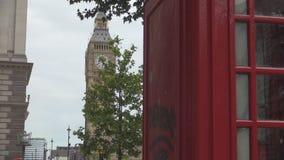 Opinión de la ciudad de Londres con una cabina de teléfono y Ben Clock grande en fondo metrajes