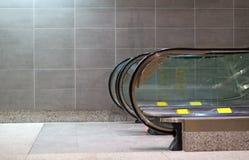 Opinión de la escalera móvil del lado con la pared tejada Foto de archivo libre de regalías
