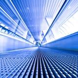 Opinión de la escalera móvil en pasillo azul Fotos de archivo