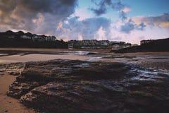 Opinión de la madrugada de la playa en el filtro retro del vintage de Polzeath Foto de archivo