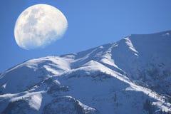 Opinión de la montaña y de la luna de la nieve fotos de archivo