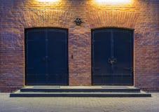 Opinión de la noche Asunto - horizonte de la ciudad de las grapas Dos puertas grandes del metal en un edificio de ladrillo rojo L fotos de archivo