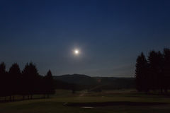 Opinión de la noche con la luna del campo de golf en el bosque de Cansiglio, Véneto, Foto de archivo