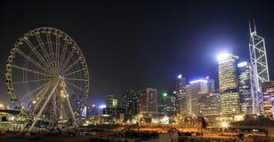 Opinión de la noche de edificios centrales así como la noria Fotografía de archivo
