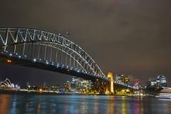 Opinión de la noche de Sydney Harbour Bridge y del teatro de la ópera en el fondo Fotos de archivo