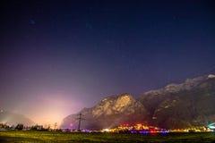 Opinión de la noche de una pequeña ciudad en las montañas Luces de la ciudad Foto de archivo