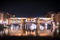 Opinión de la noche del puente de Ponte Vecchio sobre Arno River imagenes de archivo