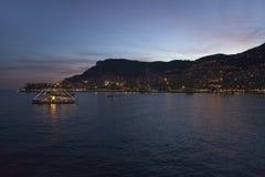 Opinión de la noche del yate y de la playa de Monte Carlo con las luces en la oscuridad, en el principado de Mónaco, Europa occid Foto de archivo libre de regalías