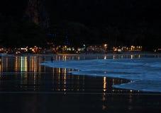 Opinión de la noche en una orilla de océano con las luces Foto de archivo