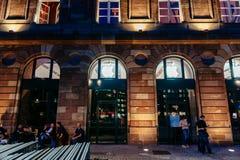 Opinión de la noche de la fachada de Apple Store builing con los clientes impacientes que esperan en cola Imagen de archivo