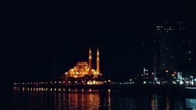 Opinión de la noche de iluminado con la mezquita de la luz del oro en la costa Costa de la tarde del tiro de la toma panorámica L almacen de video