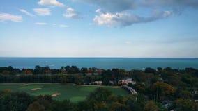 Opinión de la orilla del lago en Lincoln Park, Chicago, los E.E.U.U. Agua, cielo y nubes Tarde del otoño