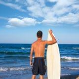Opinión de la parte posterior de la persona que practica surf del muchacho que sostiene la tabla hawaiana en la playa Fotos de archivo
