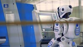 Opinión de la parte trasera de a humano-como el robot que empuja diversos botones en la pantalla del sensor en un piso industrial almacen de video