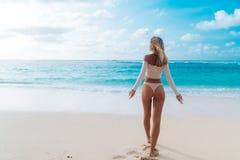 Opinión de la parte trasera la muchacha con botín en el bikini beige del color que descansa sobre la playa abandonada imagenes de archivo