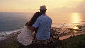 Opinión de la parte trasera, par de los amantes que miran puesta del sol hermosa, abrazando, cámara lenta almacen de video