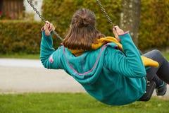 Opinión de la parte trasera un adolescente con ropa colorida en un oscilación imágenes de archivo libres de regalías