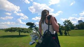 Opinión de la parte trasera una mujer que camina con los accesorios del golf metrajes