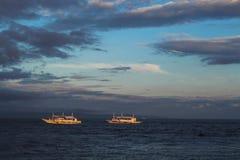 Opinión de la playa durante puesta del sol Panorama azul marino del mar con las siluetas blancas de los barcos Fotos de archivo