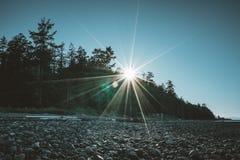 Opinión de la playa de la isla de Vancouver sobre un cielo azul claro con sunstar y la Costa del Pacífico Canadá imagen de archivo