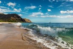 Opinión de la playa de Makua de la onda con montañas hermosas y un velero en el fondo fotografía de archivo