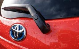 Opinión de la puerta posterior de un vehículo de motor híbrido manufacturado nuevo, japonés, visto después de una ducha de lluvia imagenes de archivo