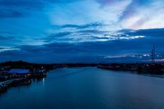 Opinión de la puesta del sol de la ciudad y del río Foto de archivo