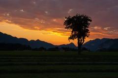 Opinión de la puesta del sol con las nubes sobre las montan@as Foto de archivo libre de regalías
