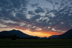 Opinión de la puesta del sol con las nubes sobre las montan@as Imágenes de archivo libres de regalías