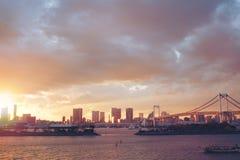Opinión de la puesta del sol de la línea de ciudad y del puente del arco iris fotografía de archivo libre de regalías