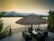 Opinión de la puesta del sol de la orilla en el kampot Camboya Asia con los sofás de la cubierta fotografía de archivo