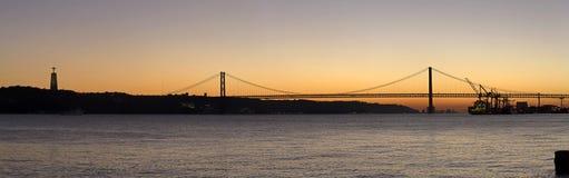 Opinión de la puesta del sol de los 25 de Abril Bridge en Lisboa, Portugal Imagen de archivo libre de regalías