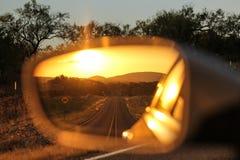 Opinión de la puesta del sol en un espejo de la vista posterior en el coche fotografía de archivo