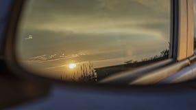 Opini?n de la puesta del sol del espejo posterior de un coche foto de archivo libre de regalías