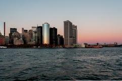 Opinión de la puesta del sol del horizonte de New York City del barco a Ellis Island fotografía de archivo libre de regalías