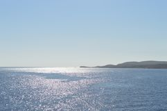 Opinión de la puesta del sol de la isla de Comino con la luz reflectora foto de archivo libre de regalías