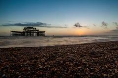 Opinión de la puesta del sol sobre el embarcadero y la playa viejos de Brighton Imagen de archivo